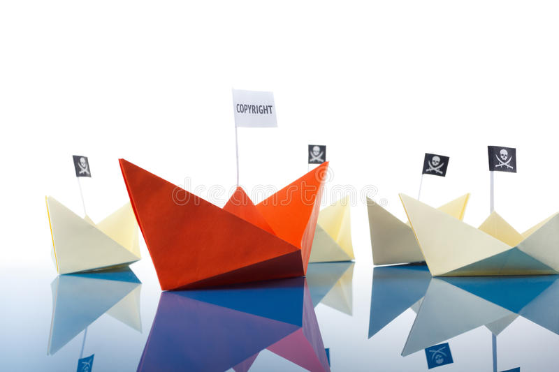 Ship and several pirate boats. Paper origami ship and several pirate Vessel with black flag Jolly Roger royalty free stock image