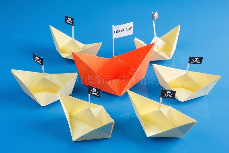 Ship and several pirate boats. Paper origami ship and several pirate Vessel with black flag Jolly Roger stock photography