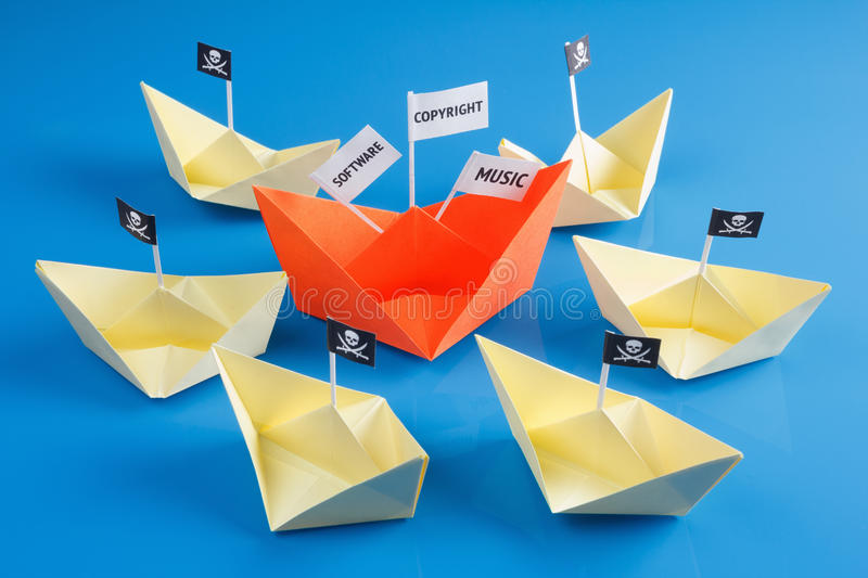 Ship and several pirate boats. Paper origami ship and several pirate Vessel with black flag Jolly Roger stock image