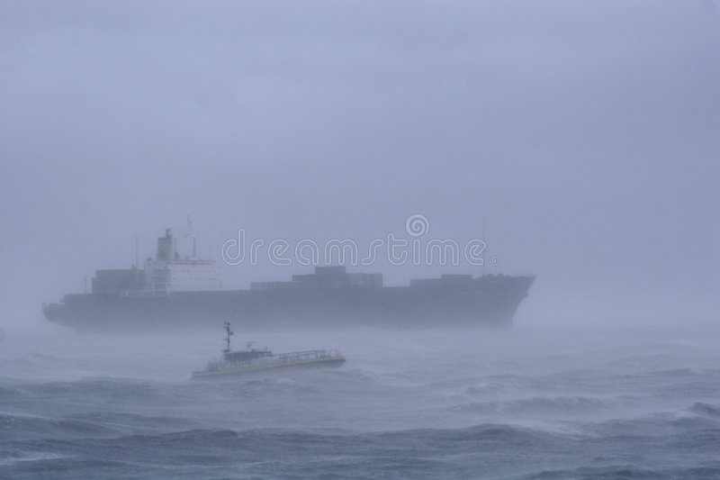 Ship in a Storm. A large cargo ship leaves the harbor at Flushing (Vlissingen), the Netherlands in a heavy storm