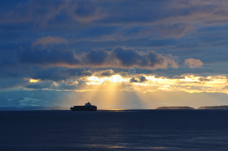 Ship traveling in sunset stock photography