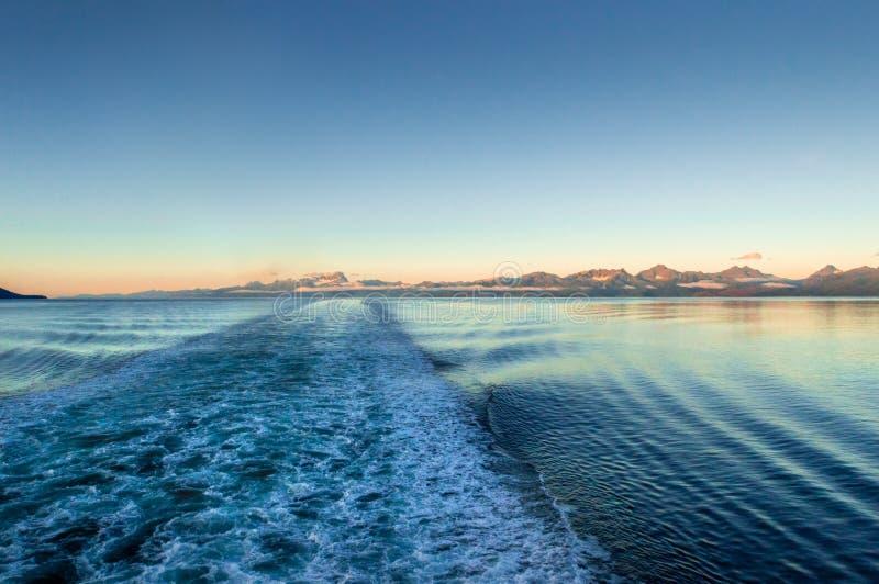 Ship wake at dawn, lighting rugged mountains across ocean channel. Alaska, USA. Ship`s ocean wake at dawn with sunrise light upon rugged mountains across ocean stock images