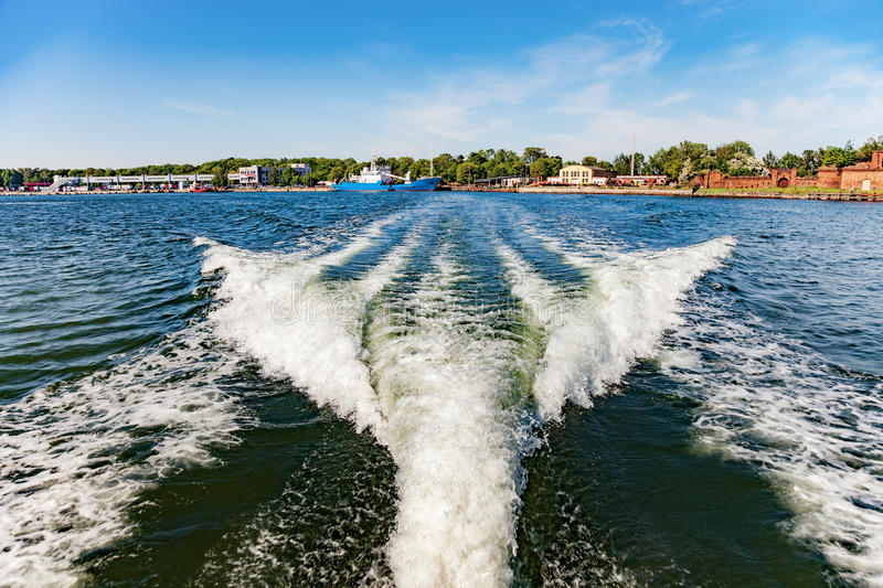 Ship wake on water. Ship white wake on blue water and sky stock image