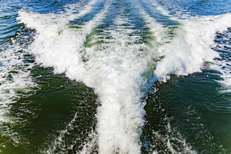 Ship wake on water. Ship white wake on blue water and sky royalty free stock photography