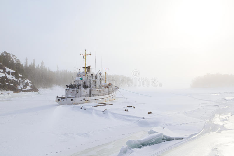 The ship which has frozen in in ice in a winter bay in the foggy. Morning. Barents sea stock photos