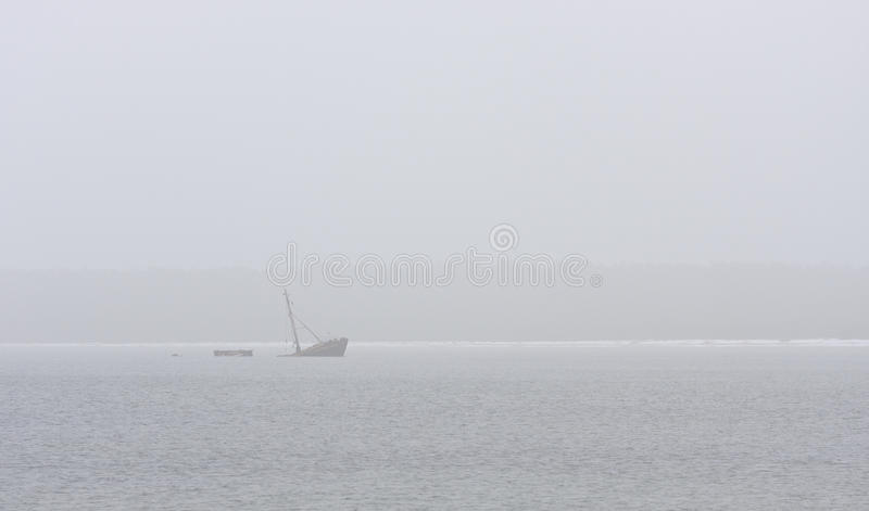Ship wreck. A ship wreck of an old fishing ship in a sea near coastline at a very misty weather royalty free stock photos