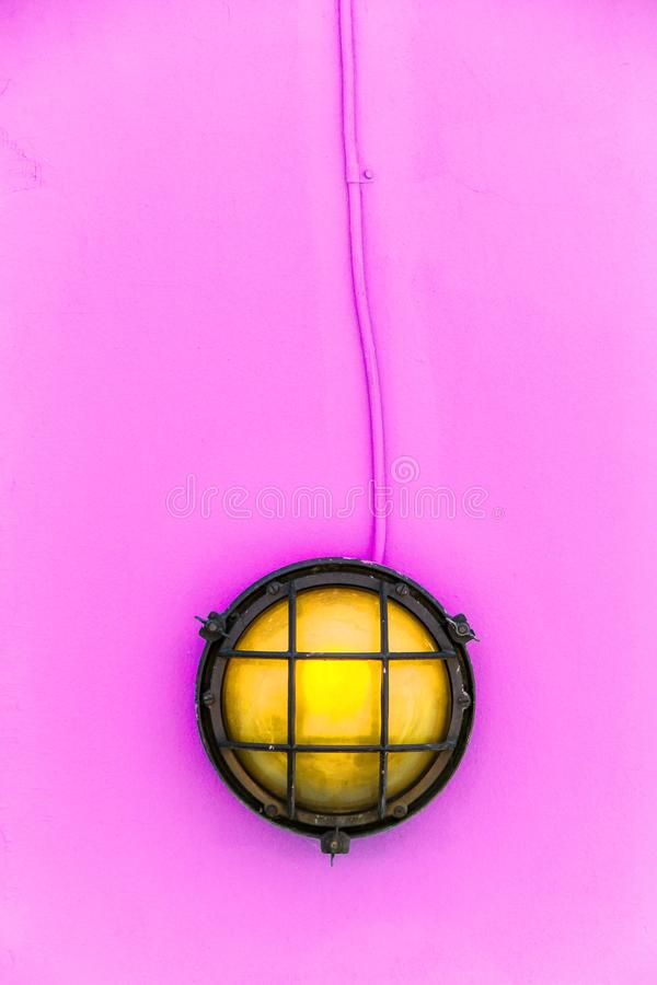 Ship yellow deck lamp bulkhead light surrounded by a metal rusted frame fixed to a painted light pink wooden wall. And similarly pastel pink color painted royalty free stock image