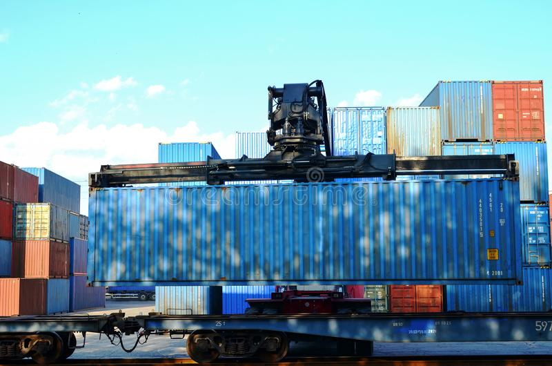 Shipping container loading by richtracker on the freight rail car at logistic warehouse port. stock photography