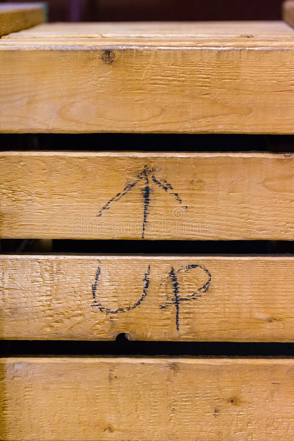 Shipping Crate with Up on Slat. A close up of an old shipped crate box with Up and an arrow in pencil on a slat stock photos