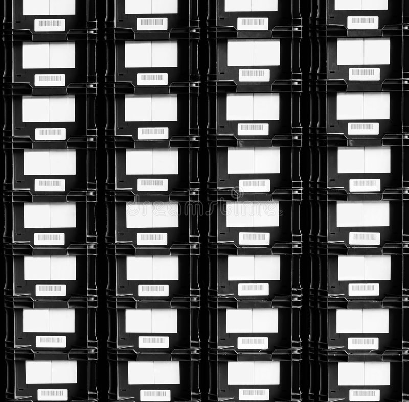 Shipping Crates. Stacks of black plastic shipping crates, with blank kan-ban labels and barcodes. Automotive component shipping stock image