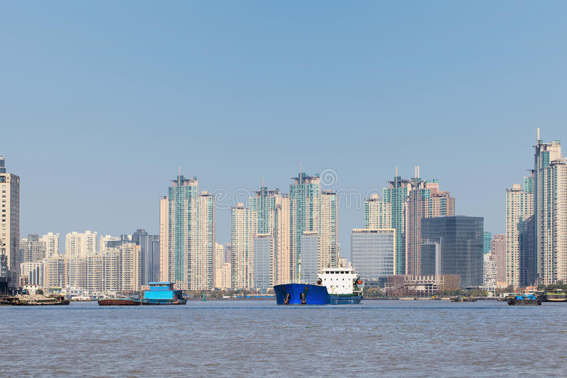 Shipping at Huangpu River with apartment buildings on background, Shanghai, China. Shipping at Huangpu River with massive apartment buildings on background stock photos