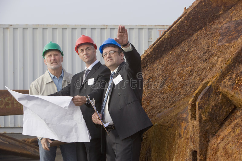 Shipping inspection engineers with plans royalty free stock photography