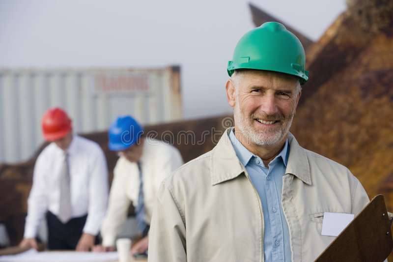 Shipping inspection engineers with plans royalty free stock image
