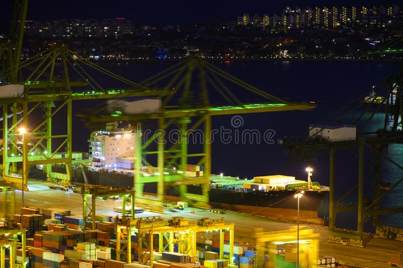 Shipping port with crane for container uploading at night royalty free stock photo