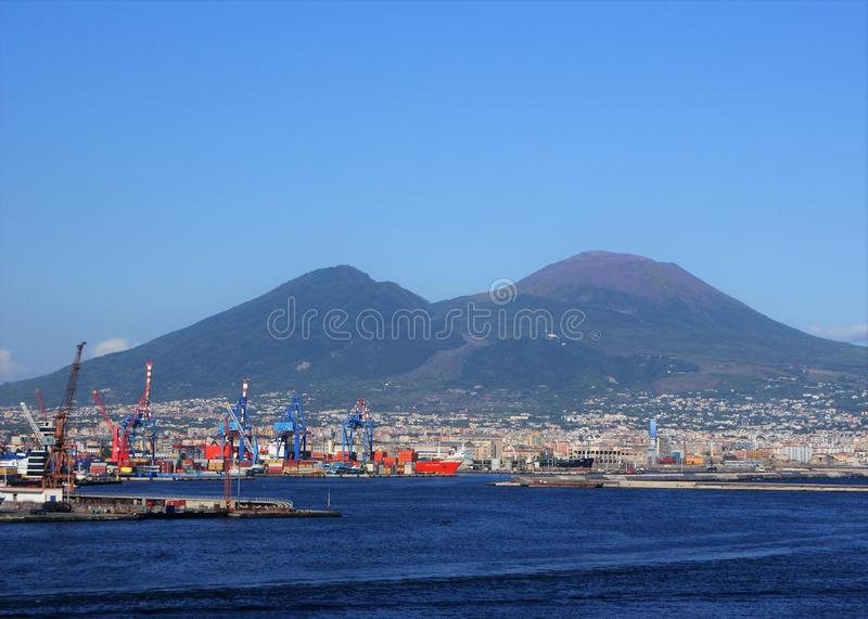 Shipping port with Mt. Vesuvius in background. Shipping containers and cranes work the busy port near Naples, Italy with Mt. Vesuvius in the background with a stock photo