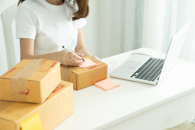 Shipping shopping online,Young start up small business owner writing address on cardboard box at workplace. Seller prepare parcel boxs of product for deliver to royalty free stock photography