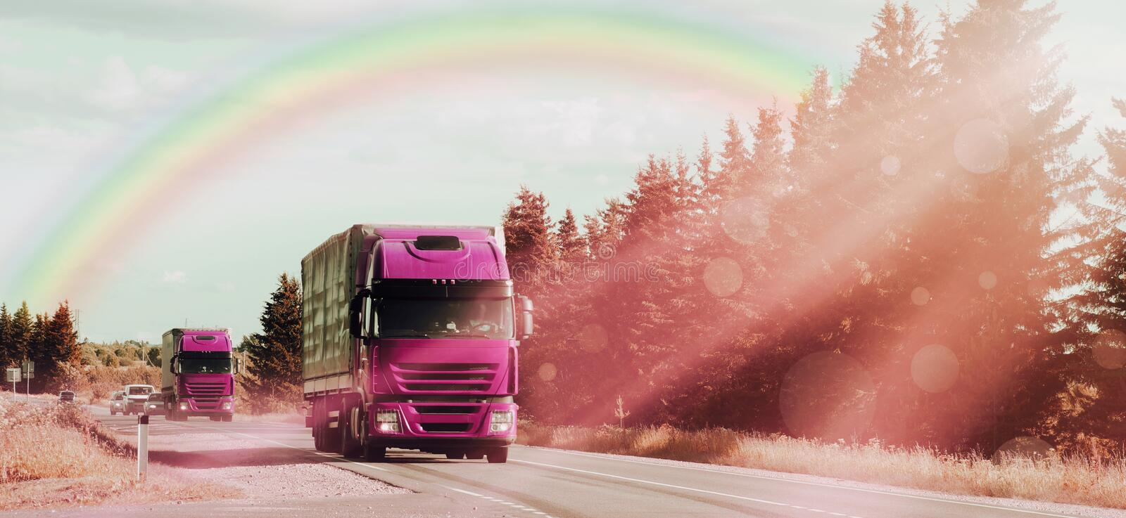 Shipping two red cargo trucks on the road being driven sun rays rainbow royalty free stock photography