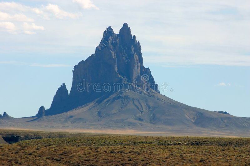 Shiprock. Monument in New Mexico on a clear day with blue cloudy skies and other rocks in the background royalty free stock photo