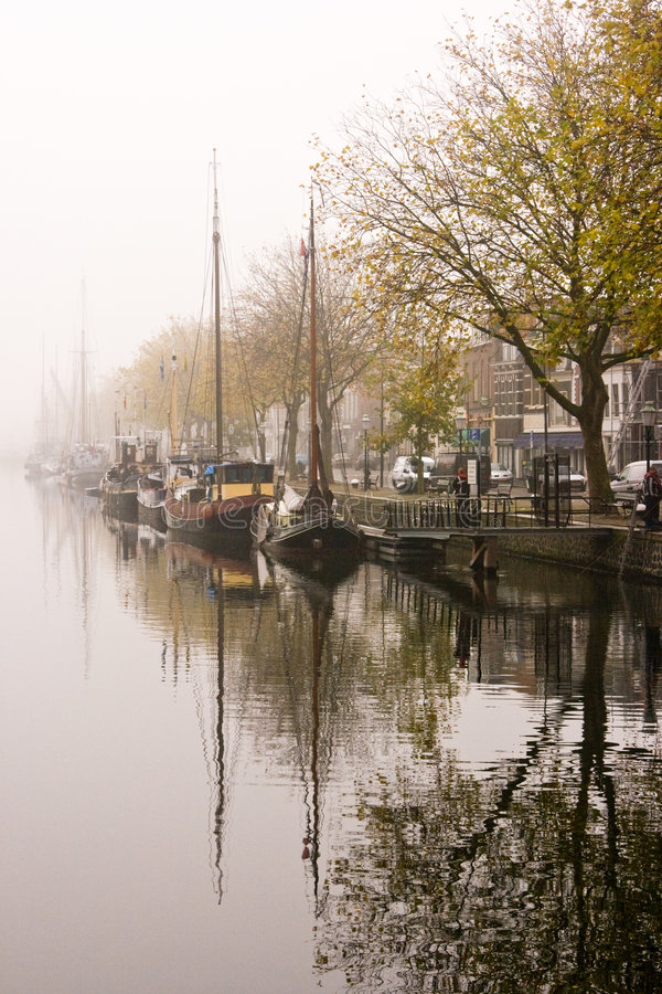 Ships. In a misty harbour and their reflection in the water royalty free stock photos