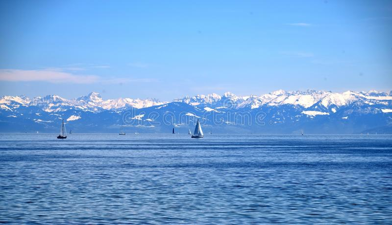 Ships on blue lake, clear blue sky, and snowy mountains, Boden Lake and Schwitzer Alps, view from Insel Mainau on spring royalty free stock photos