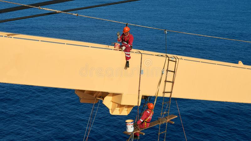 Ships crew working aloft and painting cranes. Atlantic Ocean, Open Sea - Circa March 2019: International Ships Crew Performing working aloft, crane painting stock photography