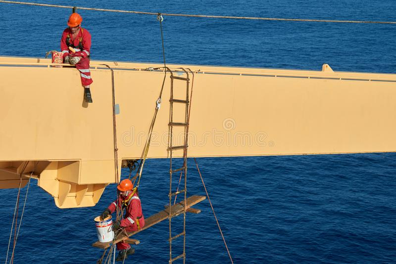 Ships crew working aloft and painting cranes. Atlantic Ocean, Open Sea - Circa March 2019: International Ships Crew Performing working aloft, crane painting stock images