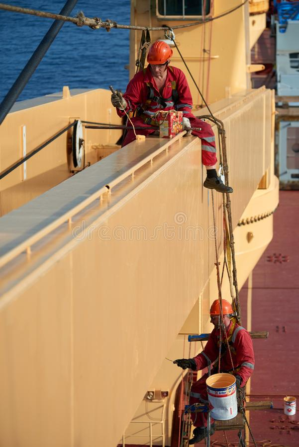 Ships crew working aloft and painting cranes. Atlantic Ocean, Open Sea - Circa March 2019: International Ships Crew Performing working aloft, crane painting stock photo