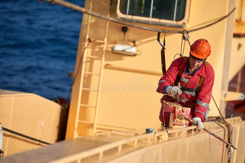 Ships crew working aloft and painting cranes. Atlantic Ocean, Open Sea - Circa March 2019: International Ships Crew Performing working aloft, crane painting royalty free stock photos