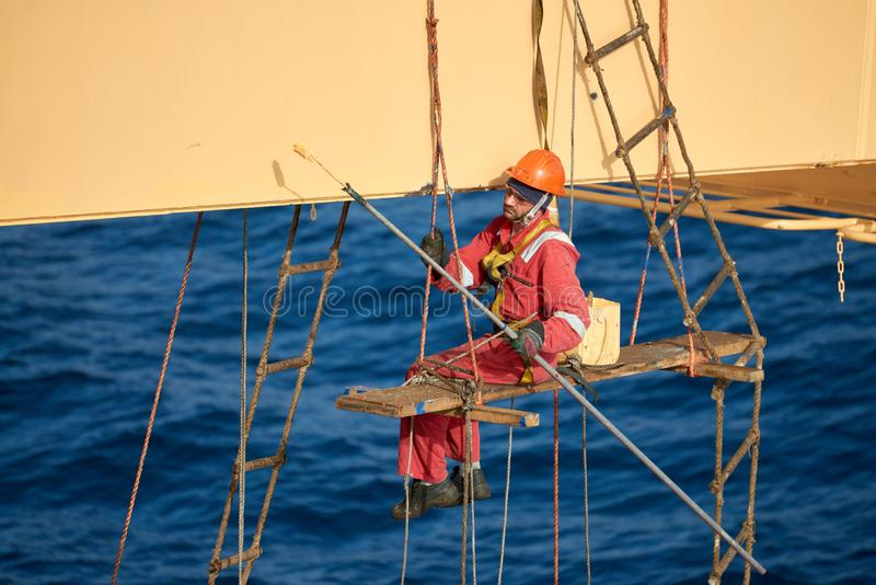 Ships crew working aloft and painting cranes. Atlantic Ocean, Open Sea - Circa March 2019: International Ships Crew Performing working aloft, crane painting royalty free stock images