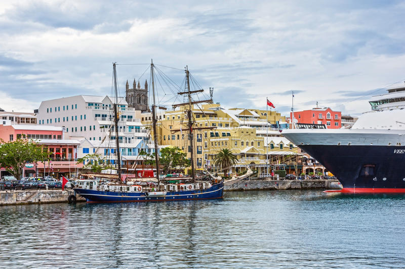 Ships Docked in Hamilton. HAMILTON,BERMUDA, MAY 25 - A tall ship and a cruise ship docked with colorful buildings along Front St. on May 25 2016 in Hamilton royalty free stock photos