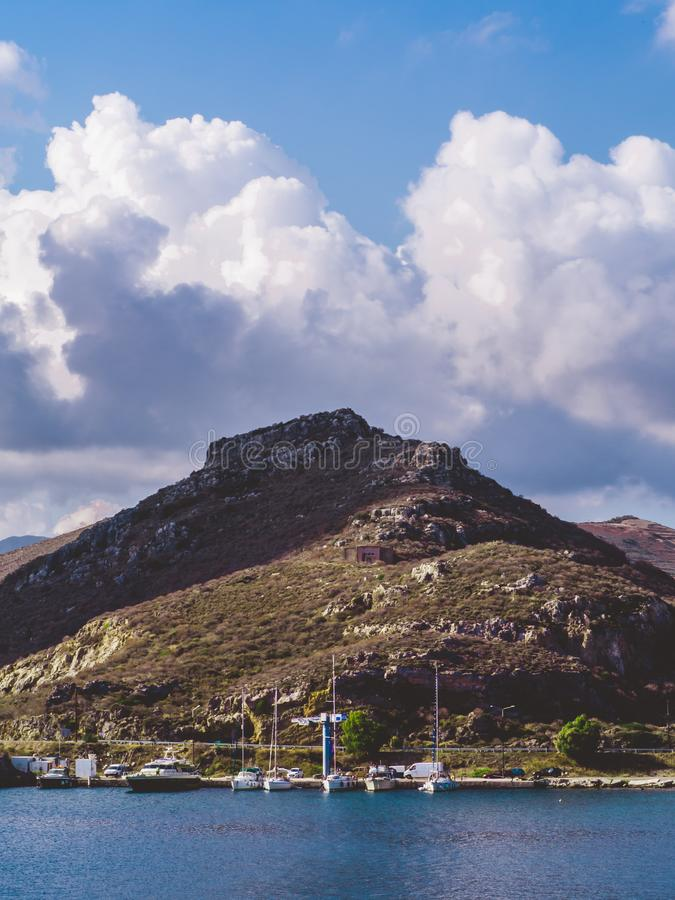 Ships docked in a small port beneath the small hill with huge clouds looming over stock photography