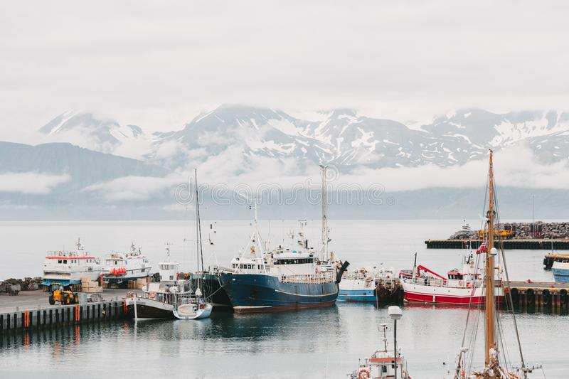 ships in harbor and beautiful snow-covered mountains on horizon in husavik, iceland royalty free stock photo