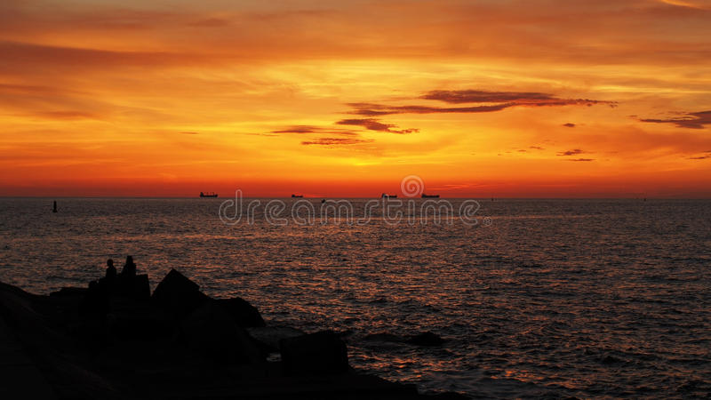 Orange sunset and ships. Sea ships at orange and red sunset stock image