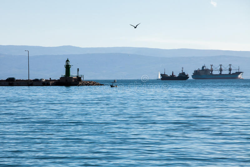 Ships at sea. Seagull flying over the sea, lighthouse and ships in the sea, sea landscape royalty free stock photo