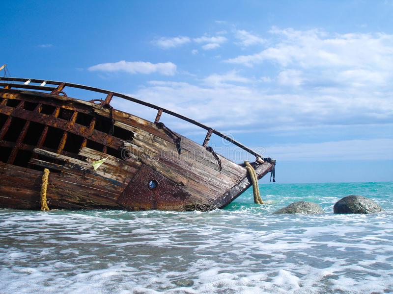 Shipwreck of a sailing ship after a storm with blue sky. Shipwreck of a battle on a beach after a storm royalty free stock photography