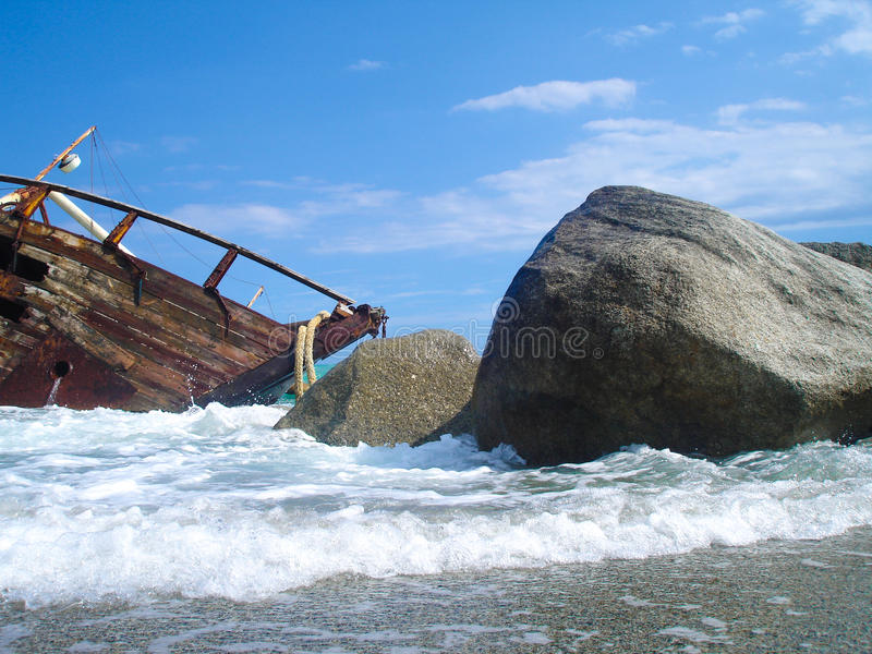 Shipwreck of a sailing ship after a storm with blue sky. Shipwreck of a battle on a beach after a storm stock images