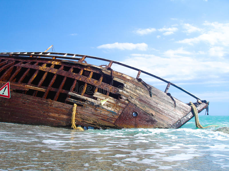 Shipwreck of a sailing ship after a storm with blue sky. Shipwreck of a battle on a beach after a storm royalty free stock image