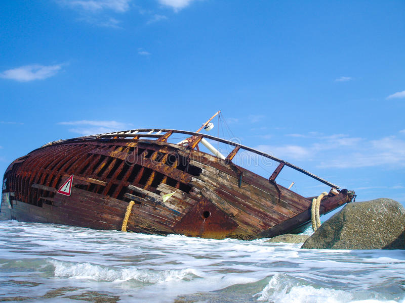 Shipwreck of a sailing ship after a storm with blue sky. Shipwreck of a battle on a beach after a storm stock photography
