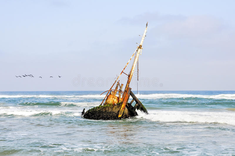 Shipwreck in the Shallow Waves. Rusted Old Shipwreck in the the Shallow Waters off the Coast of Angola, Southern Africa royalty free stock photo