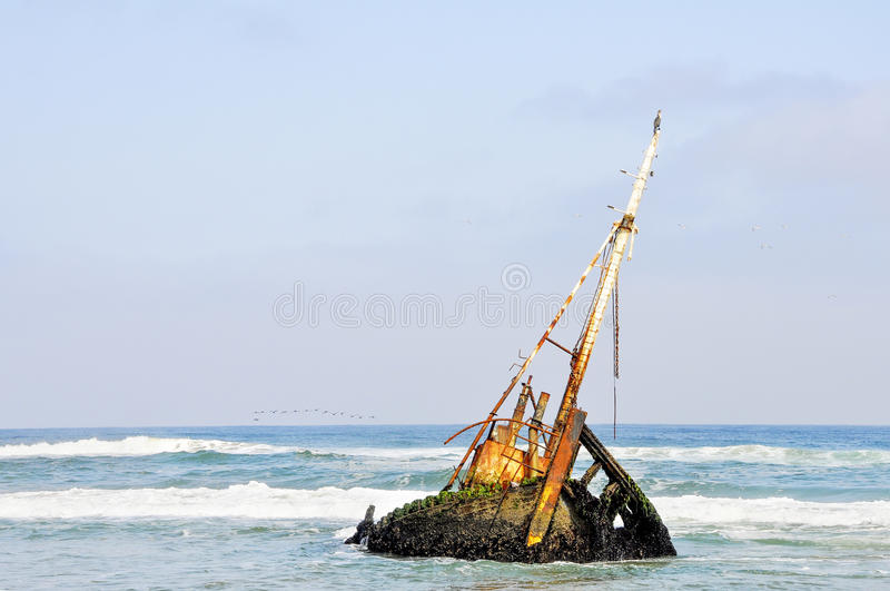 Shipwreck in the Shallow Waves. Rusted Old Shipwreck in the the Shallow Waters off the Coast of Angola, Southern Africa royalty free stock photos