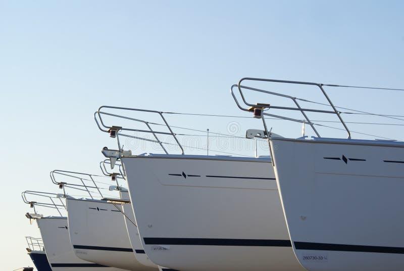 Shipyard. Some luxury yachts on shipyard on blue background royalty free stock images