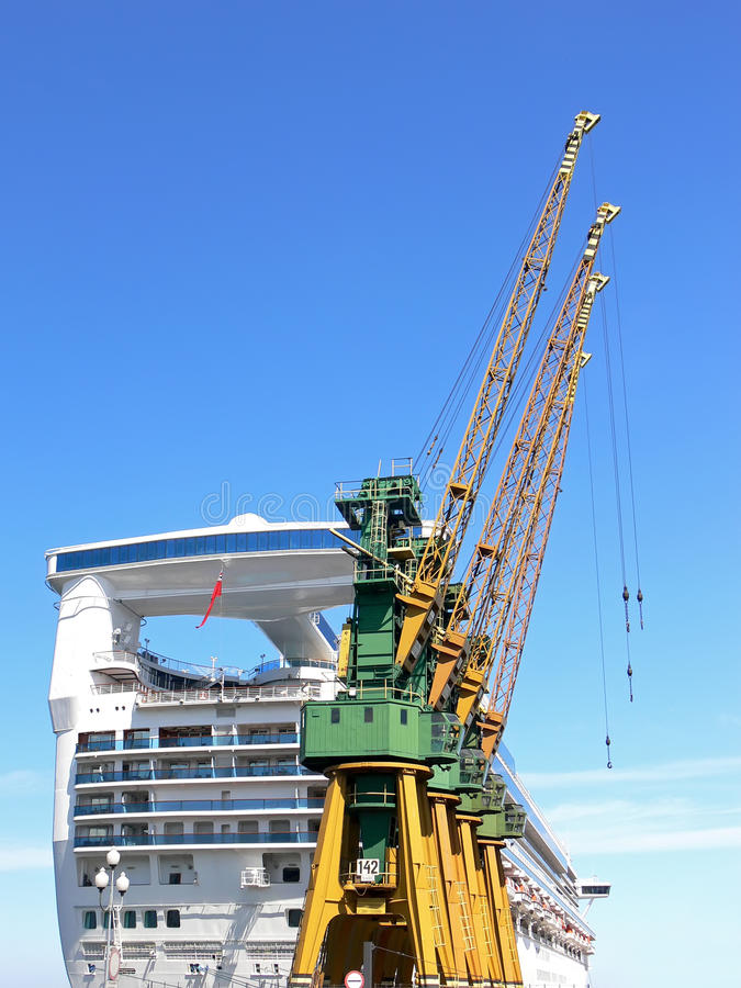 Shipyard cranes. With huge cruis liner and blue sky in the background royalty free stock photo