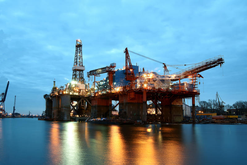 Shipyard at dusk. A view of two large waterfront drilling platforms used in shipbuilding yards stock images