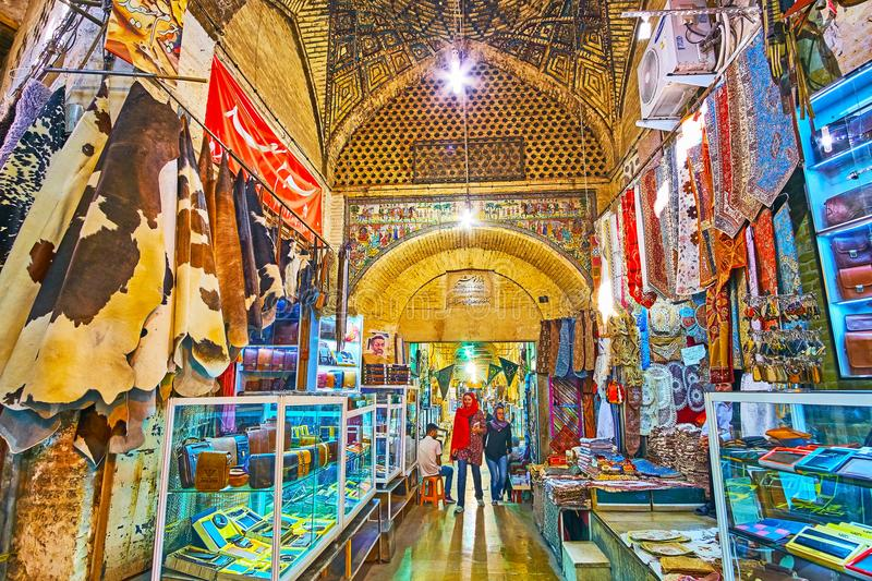 Discover Shiraz market, Iran. SHIRAZ, IRAN - OCTOBER 12, 2017: The narrow alley with small stalls on both sides leads to the entrance to Moshir Bazaar, on royalty free stock photo