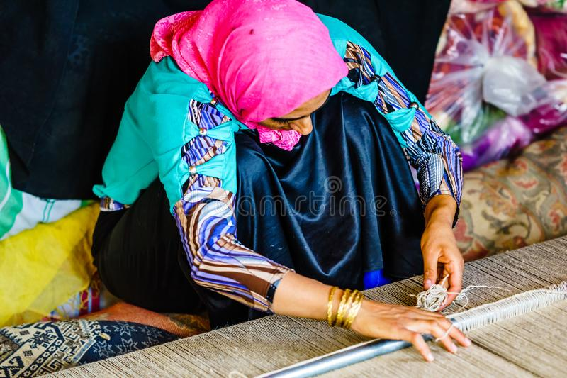 Shiraz, Iran on October 25th 2016, woman weaving carpet. Shiraz, Iran on October 25th 2016, View on woman weaving carpet stock image