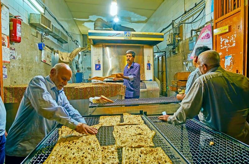 SHIRAZ, IRAN - OKTOBER 13, 2017: De oude bakkerijwerken in de avond, cliënten komen na het werk en wachten op verse flatbread,  stock afbeelding