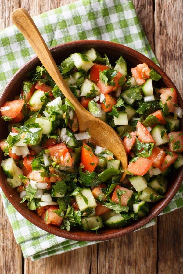 Shirazisalade van komkommers, tomaten, uien en kruidenclose-up in een kom Verticale hoogste mening stock foto