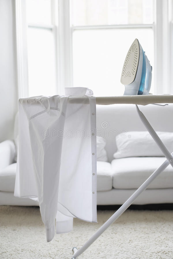 Shirt And Iron On Ironing Board. White shirt on ironing board in living room stock photos