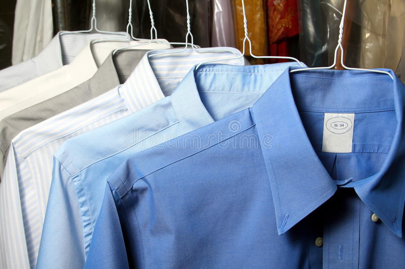 Shirt ironed in dry cleaner. Hanging on hangers stock photos