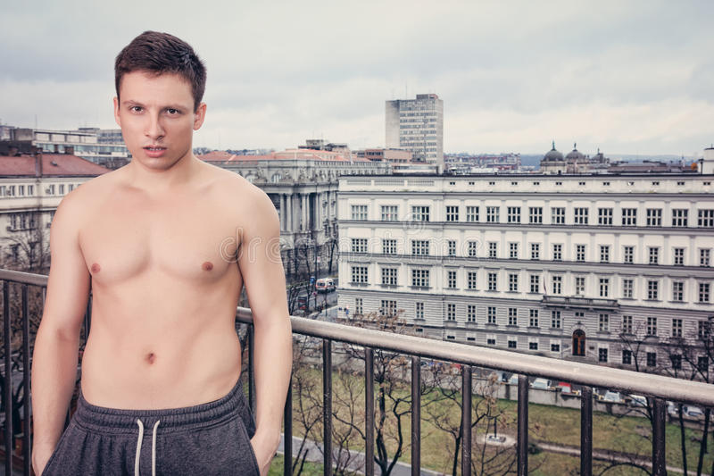 Shirtles handsome young man in sweatpants standing on terrace. With city view , Average fit guy posing on balcony in misty morning royalty free stock images